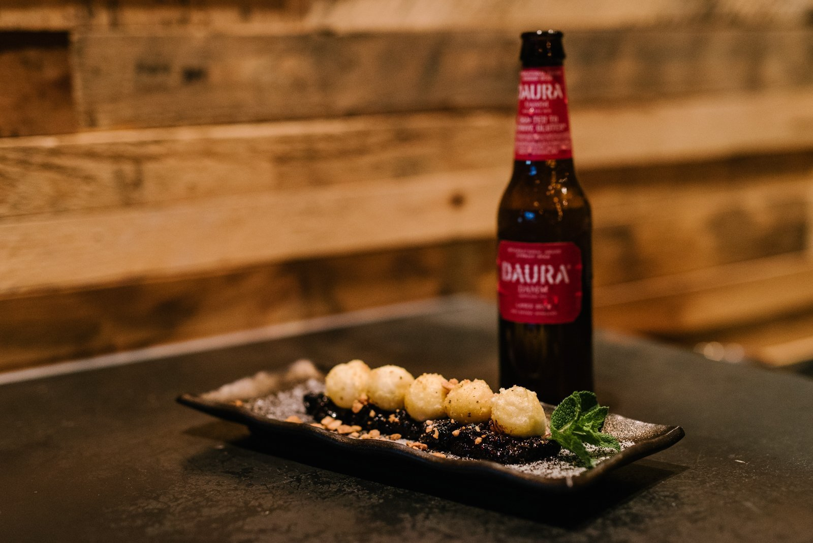 Bottle of Daura Damm with Let Your Backbone Slide (sesame mochi) at Kanpai Snack Bar in Toronto