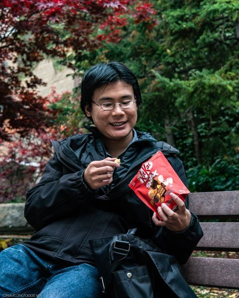 Travelling Foodie Raymond Cua enjoying KITKAT Snax at a park during fall in Toronto, Ontario