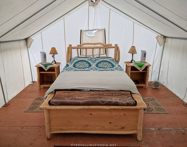 Queen bed inside glamping tent at WildExodus in Timmins, Ontario