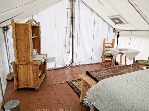 Log furniture inside glamping tent at WildExodus in Timmins, Ontario