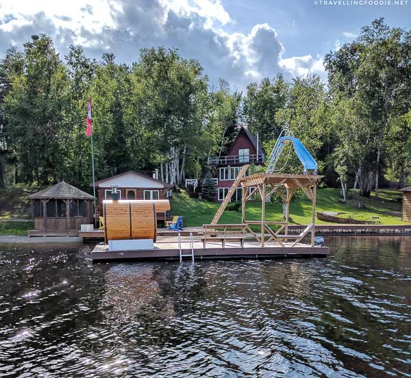 Cottage dock with sauna and slide during pontoon boat cruise