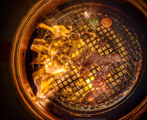 Grilling meat with flames at Gyu-Kaku Japanese BBQ in Torrance, California
