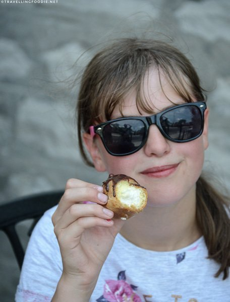 Girl holding cream puff at Urban Patisserie in Port Dover, Norfolk County, Ontario