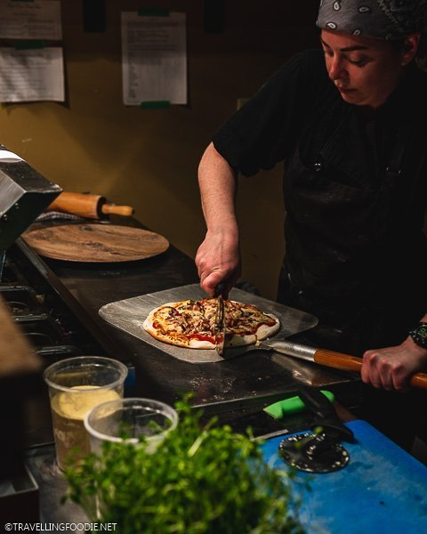 Chef slicing pizza at Clock Tower Bistro in Strathroy, Ontario