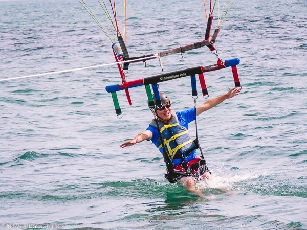 Travelling Foodie Raymond Cua knee deep in water at Daytona Beach Parasailing