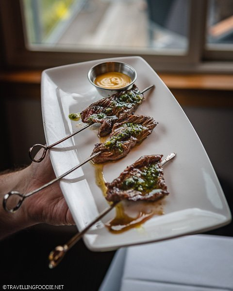 Holding Plate of Bison on Stick at Aurum Food and Wine