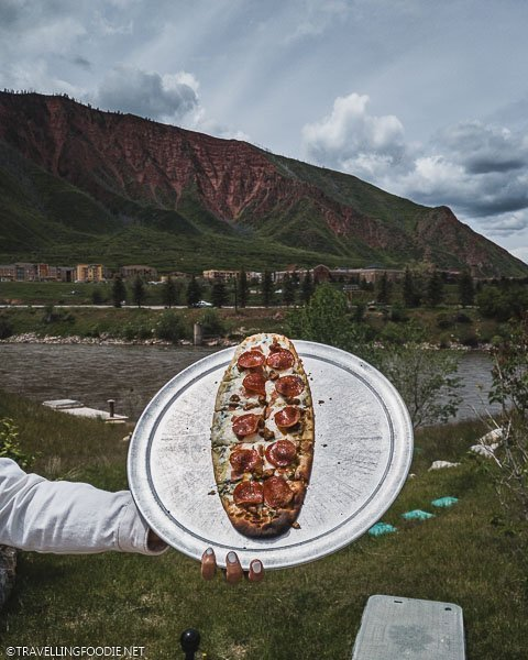 Lady holding Meat Lovers Pizza at Iron Mountain Hot Springs