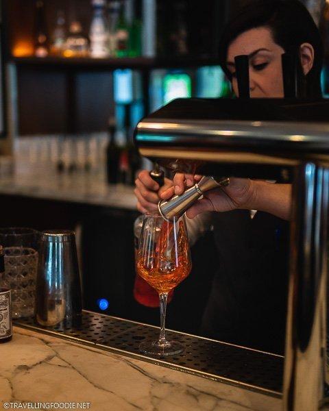 Bartender making Aperol Spritz at The Lobbyist inside Le Méridien Denver Downtown