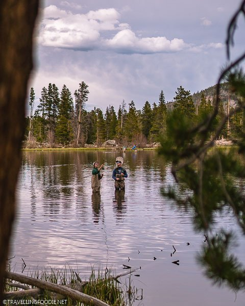 Woman trying to fly fish at Sprague Lake in Rocky Mountain National Park Colorado