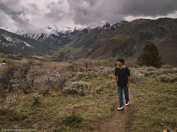 Travelling Foodie Raymond Cua walking the trail with background of Capital Peak in Colorado