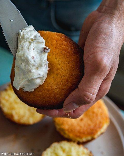 Holding Prosciutto and Cheese Cupcake to apply Prosciutto Buttercream