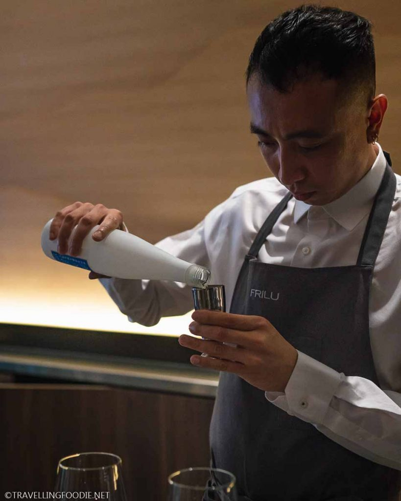 Bartender pouring sake on jigger