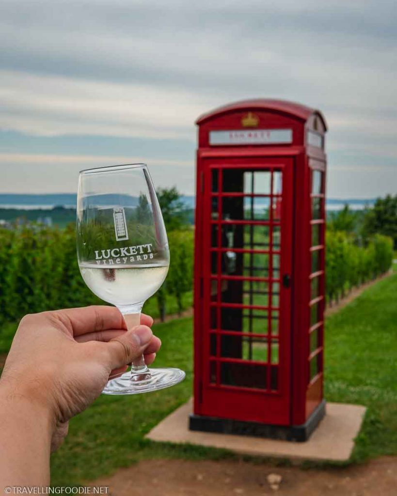 Holding Wine Glass on Red Phone Booth at Luckett Vineyards in Wolfville, Nova Scotia