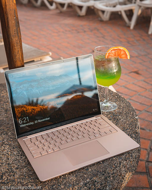 Microsoft Surface Laptop 3 with a cocktail on pool table