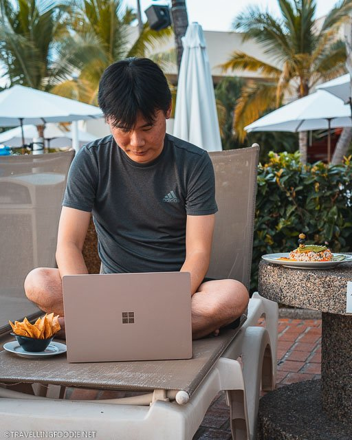 Travelling Foodie Raymond Cua sitting on pool chair using Microsoft Surface Laptop 3 with nachos and tuna