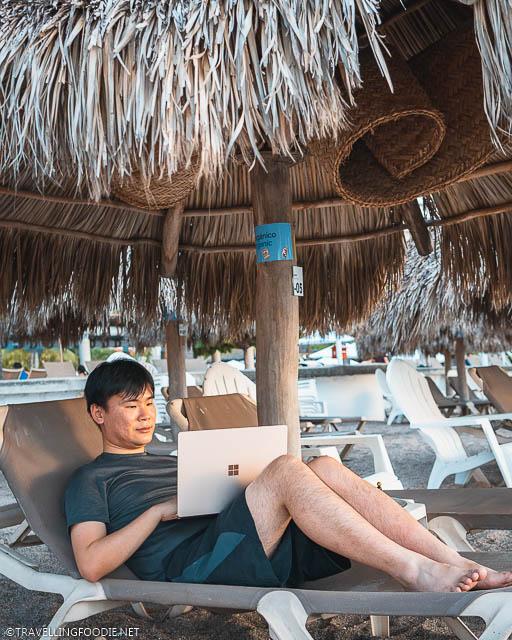 Travelling Foodie Raymond Cua lying on the cabana using Microsoft Surface Laptop 3