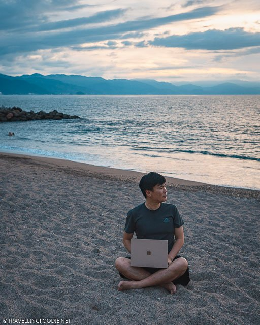 Travelling Foodie Raymond Cua sitting on the sand using Microsoft Surface Laptop 3
