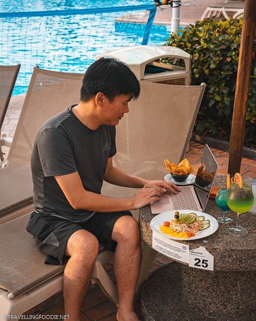 Travelling Foodie Raymond Cua sitting on pool chair using Microsoft Surface Laptop 3 on a table