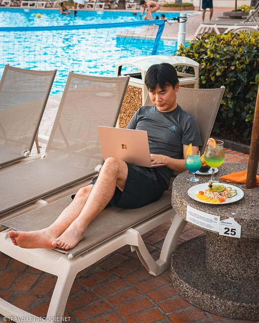 Travelling Foodie Raymond Cua lying on the pool chair using Microsoft Surface Laptop 3 with cocktails