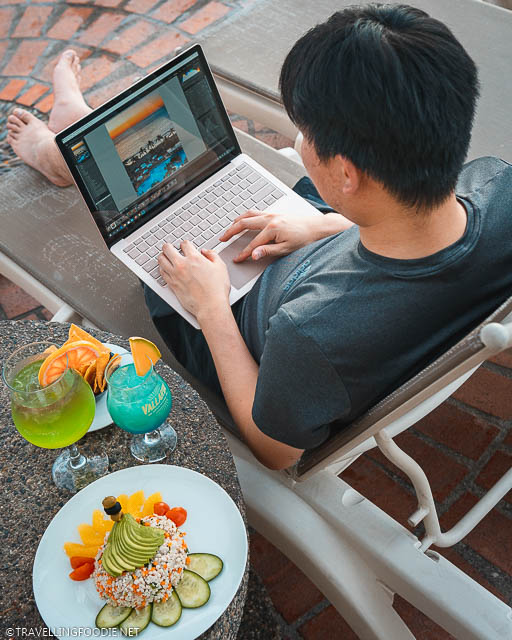 Over the shoulder of Travelling Foodie Raymond Cua editing photo on Microsoft Surface Laptop 3 with cocktails and food