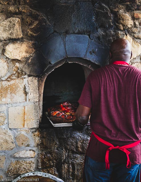Chef taking out roast pork from Dutch oven at USVI Agrifest in St. Croix