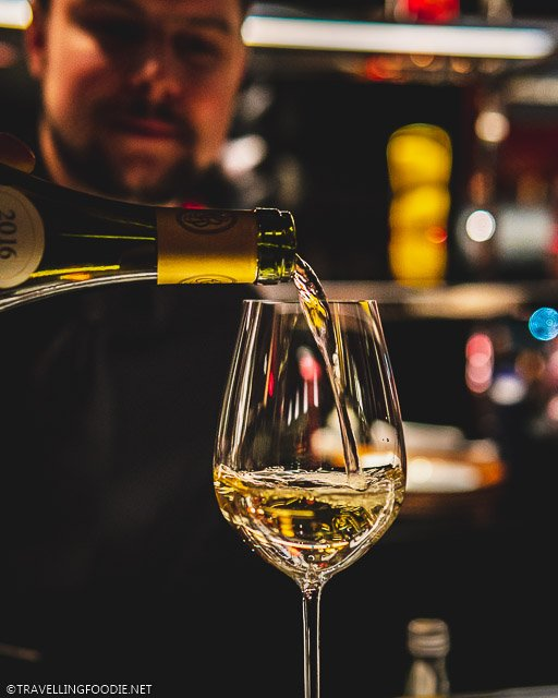 Pouring Puligny Montrachet Wine on Wine Glass at L'Atelier de Joel Robuchon for Montreal en Lumiere 2020 Tasting Menu