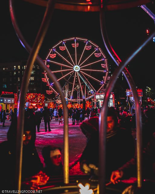 Quebec Maple Ferris Wheel framed by RBC Braziers with People at Montreal Festival of Lights