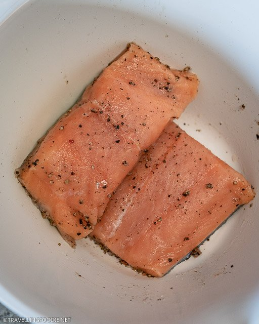 Two raw salmon fillets seasoned with salt and pepper
