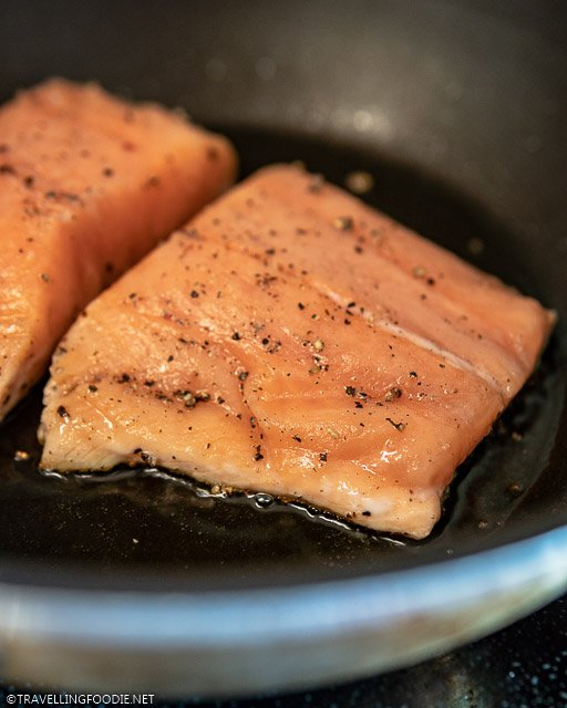 Seasoned raw salmon fillet on pan