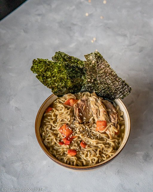 Dropping sesame seeds on a bowl of Instant Pot Thai Curry Chicken Noodle Soup