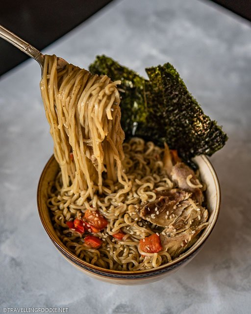 Noodle lifting the bowl of Thai Curry Chicken Noodle Soup made with Instant Pot