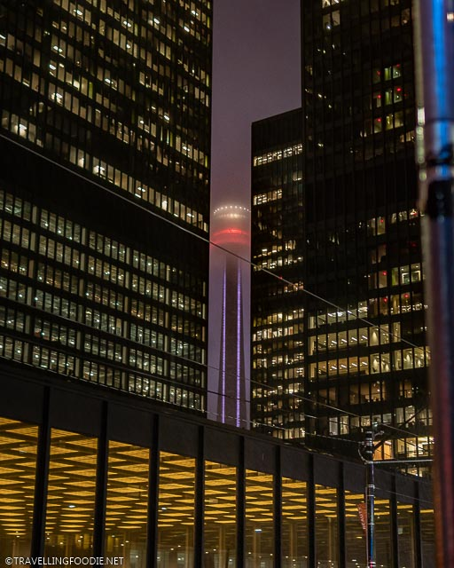 CN Tower framed by TD Buildings with yellow lights at night