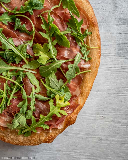 Quarter Italian Pizza of Prosciutto di Parma and Arugula with Black Pepper