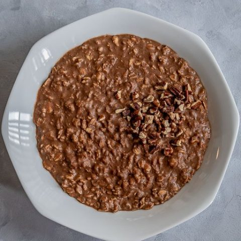 Chocolate oatmeal on white bowl topped with crushed pecans