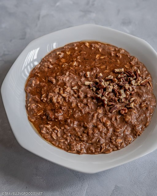 Chocolate oatmeal with crushed pecans and maple syrup toppings
