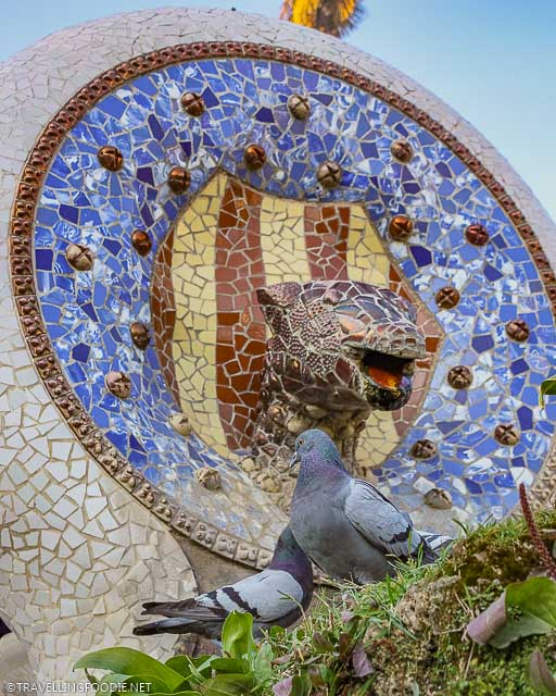 Mosaic Serpent Head Fountain at Park Guell with pigeons