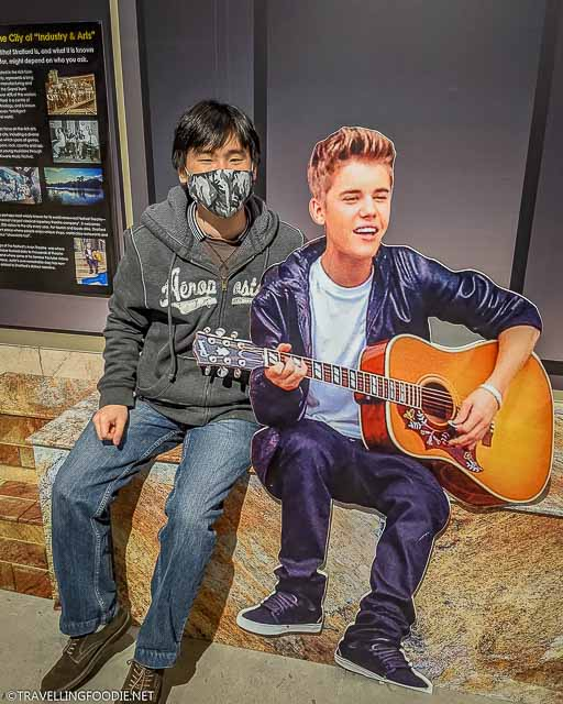 Raymond Cua of Travelling Foodie with Justin Bieber cut out at Stratford Perth Museum in Stratford, Ontario