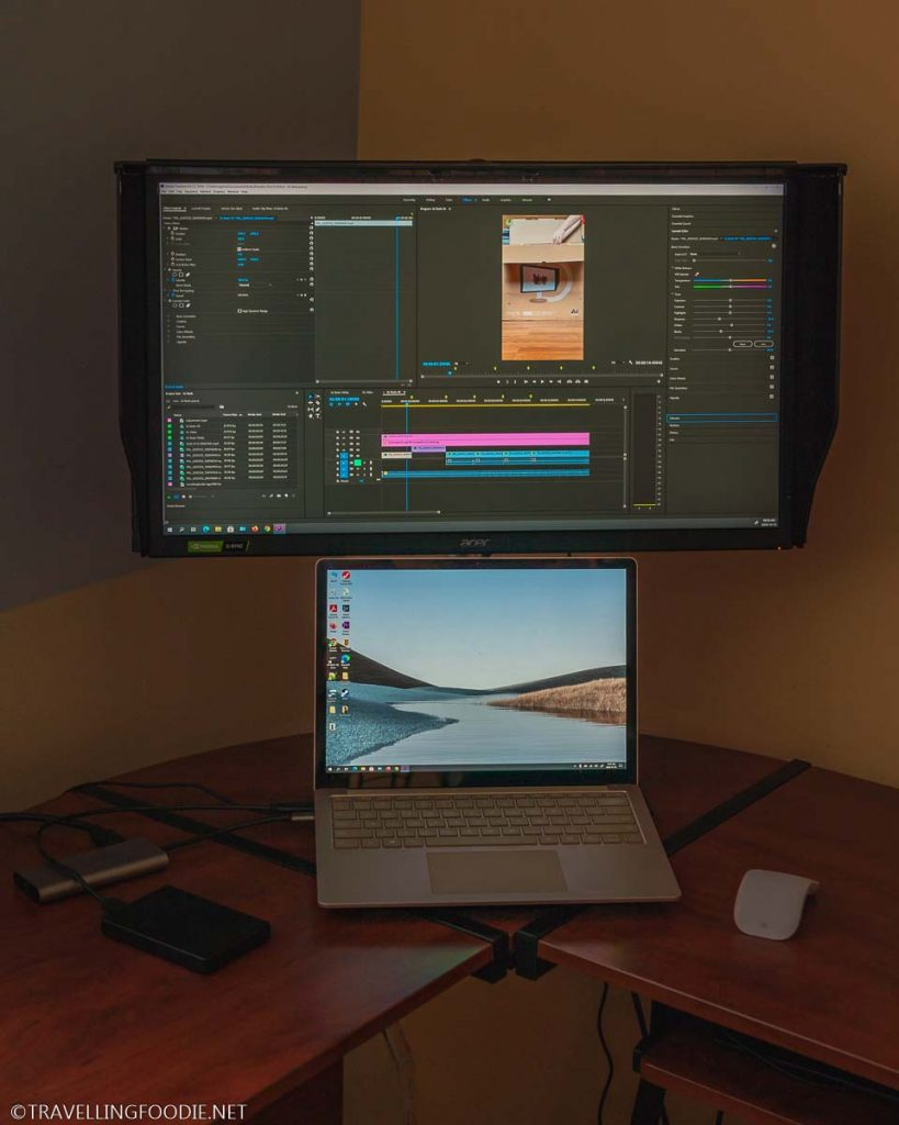 Acer ConceptD CP3 CP327K 4K Monitor showing Adobe Premiere Pro with Microsoft Surface Laptop 3 underneath