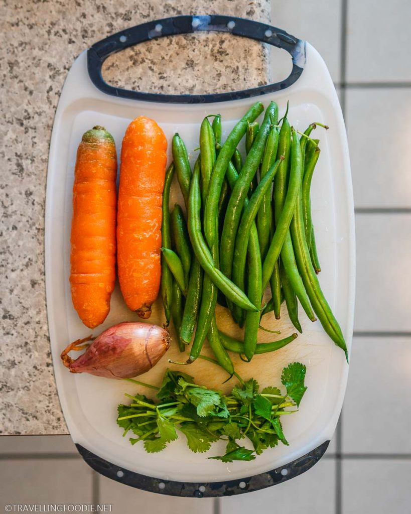Onion, Cilantro, Green Beans and Carrots on chopping board