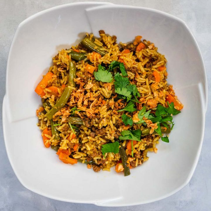 Instant Pot Beef Biryani on white bowl garnished with cilantro and crispy shallots
