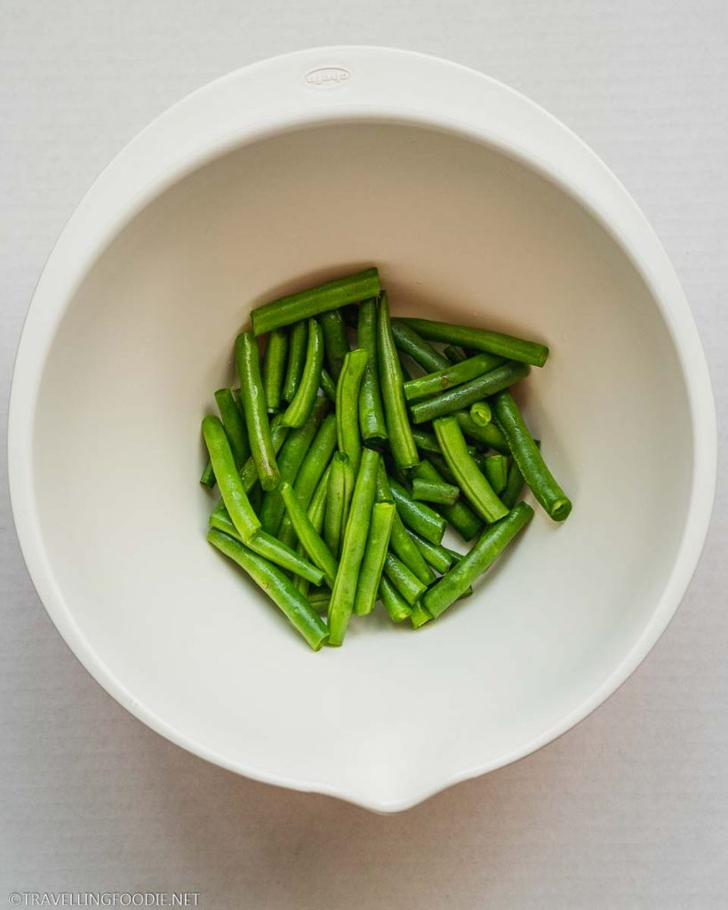 Green beans cut in half on a bowl