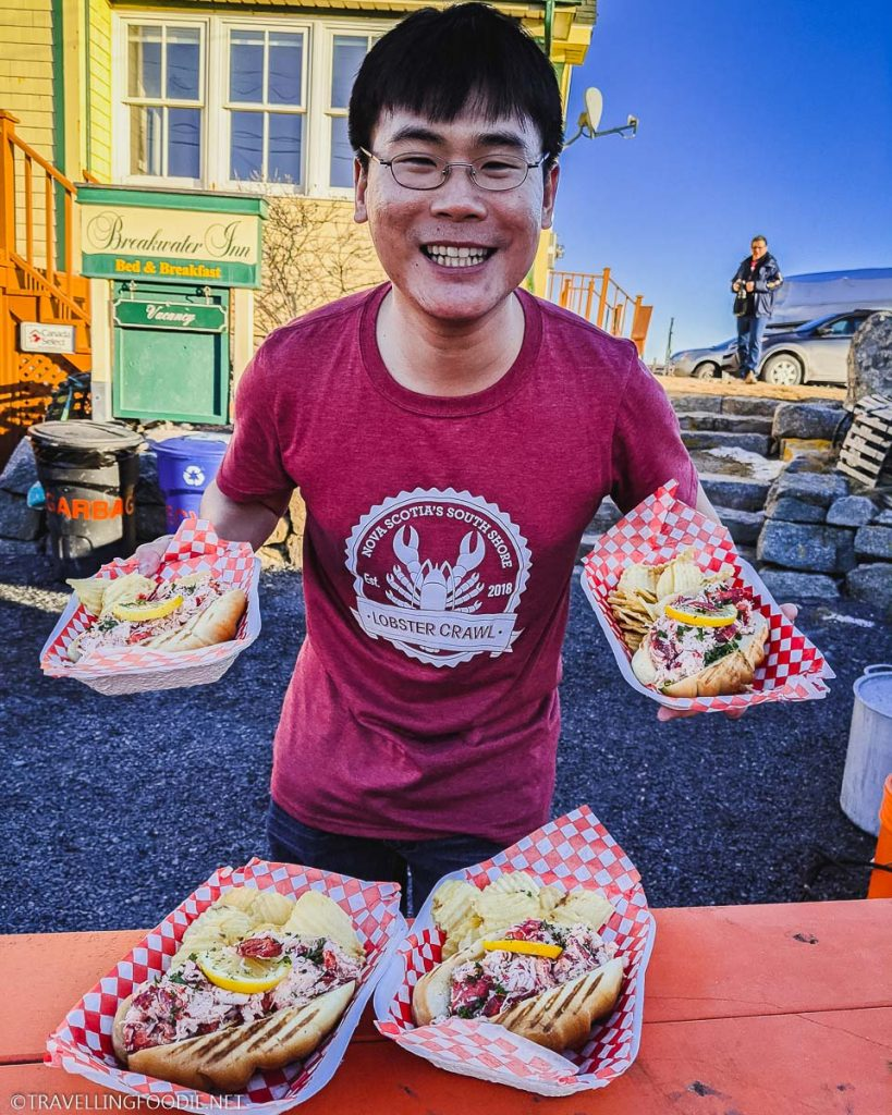 Travelling Foodie Raymond Cua with four lobster rolls at Breakwater Inn in Peggy's Cove, Nova Scotia