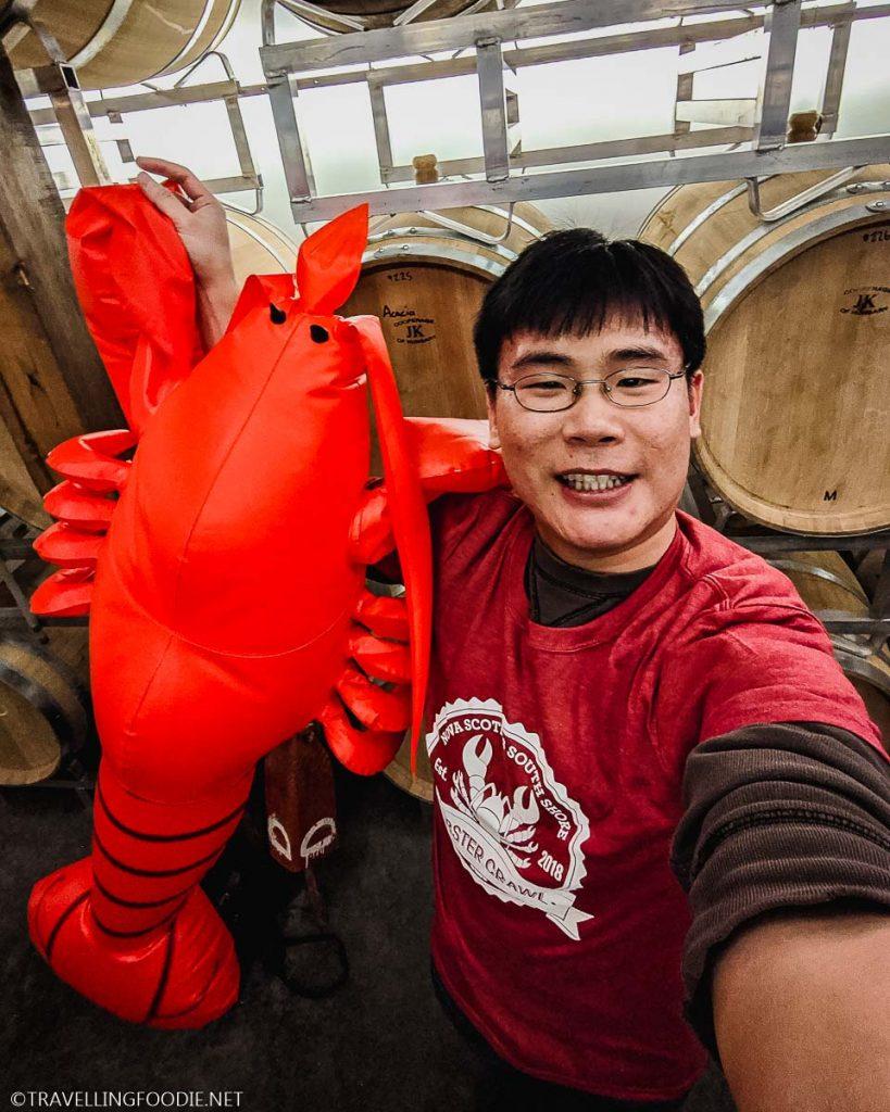 Travelling Foodie Raymond Cua holding big stuffed lobster